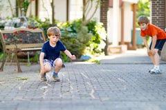 演奏在操场的两个一点学校和幼儿园孩子男孩跳房子 免版税库存照片