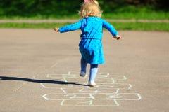 演奏在操场的小女孩跳房子 免版税库存照片