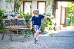 演奏在操场的小白肤金发的滑稽的孩子男孩跳房子户外 免版税库存图片