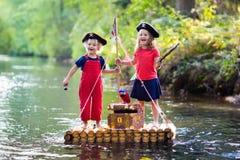 演奏在木木筏的孩子海盗冒险 免版税图库摄影