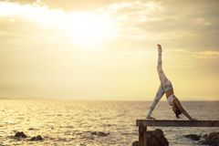演奏在木码头的妇女瑜伽姿势反对升起在s的太阳 免版税图库摄影