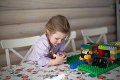 演奏在桌上的哀伤的矮小的白种人女孩建设者 免版税图库摄影