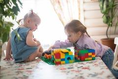 演奏在桌上的小白种人女孩姐妹建设者, 图库摄影