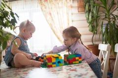 演奏在桌上的小白种人女孩姐妹建设者, 免版税库存图片