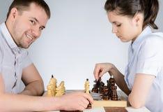 演奏在棋的妇女黑片断反对咧嘴笑的人 免版税库存照片