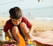 演奏在海滩夏时的小男孩沙子 图库摄影