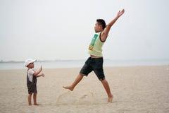演奏在海滩的父亲和儿子跃迁 免版税图库摄影