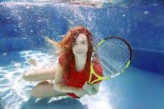 演奏在游泳池的年轻美丽的女孩网球水中 库存图片