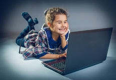 演奏在灰色背景十字架的青少年的女孩膝上型计算机 图库摄影