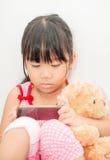 演奏在灰色背景的亚裔女孩智能手机 免版税库存图片