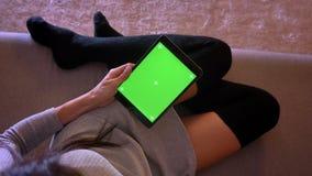演奏在片剂的年轻俏丽的女性特写镜头画象录影有绿色屏幕的 在一个舒适位置的女孩腿 股票录像