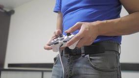 演奏在电视的人概念生活方式gamepad手录影控制台 手拿着演奏在电视的新的控制杆录影控制台 影视素材