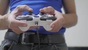 演奏在电视的人概念gamepad手录影控制台 手拿着演奏在电视的新的控制杆录影控制台 游戏玩家戏剧 股票视频