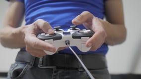 演奏在电视的人概念gamepad手录影控制台 手拿着演奏在电视的新的控制杆录影控制台 gamer 影视素材