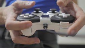 演奏在电视的人生活方式gamepad手录影控制台 手拿着演奏在电视的新的控制杆录影控制台 游戏玩家戏剧 影视素材
