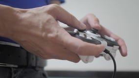 演奏在电视的人gamepad手录影控制台 手拿着演奏在生活方式电视的新的控制杆录影控制台 游戏玩家戏剧 影视素材