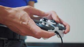 演奏在电视的人gamepad手录影控制台 手拿着演奏在电视的新的控制杆录影控制台 游戏玩家戏剧比赛 股票视频