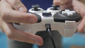 演奏在电视的人gamepad手录影控制台 手拿着演奏在电视的新的控制杆录影控制台 游戏玩家戏剧比赛与 股票录像