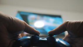 演奏在电视的录影控制台 在电视的手举行新的生活方式控制杆网上录影控制台 游戏玩家与gamepad的戏剧比赛 股票录像