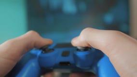 演奏在电视的录影控制台 在电视的手举行生活方式新的控制杆网上录影控制台 游戏玩家与gamepad的戏剧比赛 股票视频