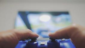 演奏在电视的录影控制台 手拿着演奏在电视的新的控制杆录影控制台 游戏玩家与gamepad的戏剧比赛 股票录像