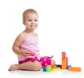 演奏在白色的孩子女孩玩具块 免版税库存照片