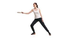 演奏在白色的年轻愉快的妇女飞碟 免版税图库摄影
