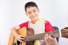 演奏在白色背景的小男孩经典吉他路线 免版税图库摄影