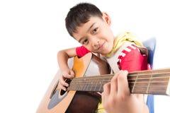 演奏在白色背景的小男孩经典吉他路线 免版税库存图片