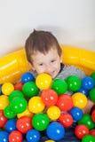 演奏在的小微笑的男孩在五颜六色的球操场 免版税库存图片