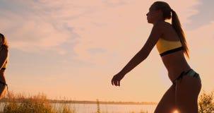 演奏在空气和罢工的运动女孩沙滩排球跃迁在网的球在一个美好的夏天晚上 股票录像