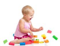 演奏在空白背景的愉快的孩子玩具块 库存图片