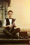 演奏在老城市s背景的时髦的行家人单簧管  免版税库存图片