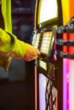 演奏在老自动电唱机的歌曲的男性手按的按钮 库存图片