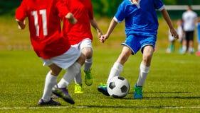 演奏在自然草沥青的孩子足球体育 免版税库存照片