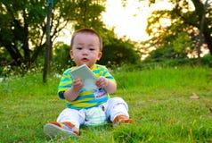 演奏在草坪(亚洲中国)的男孩/婴孩手机 免版税库存照片