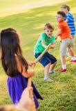 演奏在草的孩子拔河 免版税库存图片