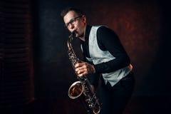 演奏在萨克斯管的男性萨克斯管吹奏者古典爵士乐 免版税库存照片