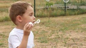 演奏在街道上的愉快的小男孩吹的肥皂泡 在风的肥皂的飞行 股票录像