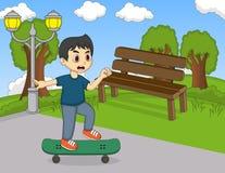 演奏在街道动画片的小男孩滑板 图库摄影