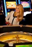 演奏在赌博娱乐场和赢取的年轻白肤金发的妇女轮盘赌 库存照片