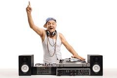 演奏在转盘的音乐和举行他的fi的快乐的老DJ 免版税图库摄影