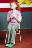 演奏在音乐课的女孩长笛 免版税库存图片