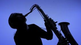 演奏在黑暗的年轻人萨克斯管。特写镜头 股票录像