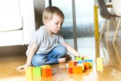 演奏在他的房子里面的孩子玩具块 免版税库存图片
