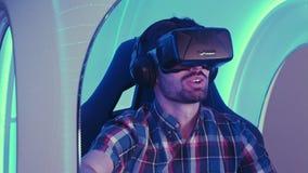演奏在3D虚拟现实模拟器的愉快的年轻人计算机游戏 库存照片