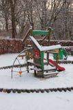 演奏地面的公开孩子在与雪的冬天 免版税库存图片