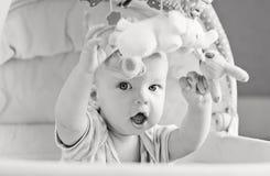 演奏坐在摇篮的婴孩 库存图片