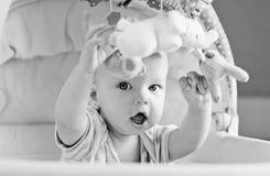 演奏坐在摇篮的婴孩 免版税库存图片