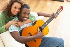 演奏坐的沙发年轻人的夫妇吉他 库存照片